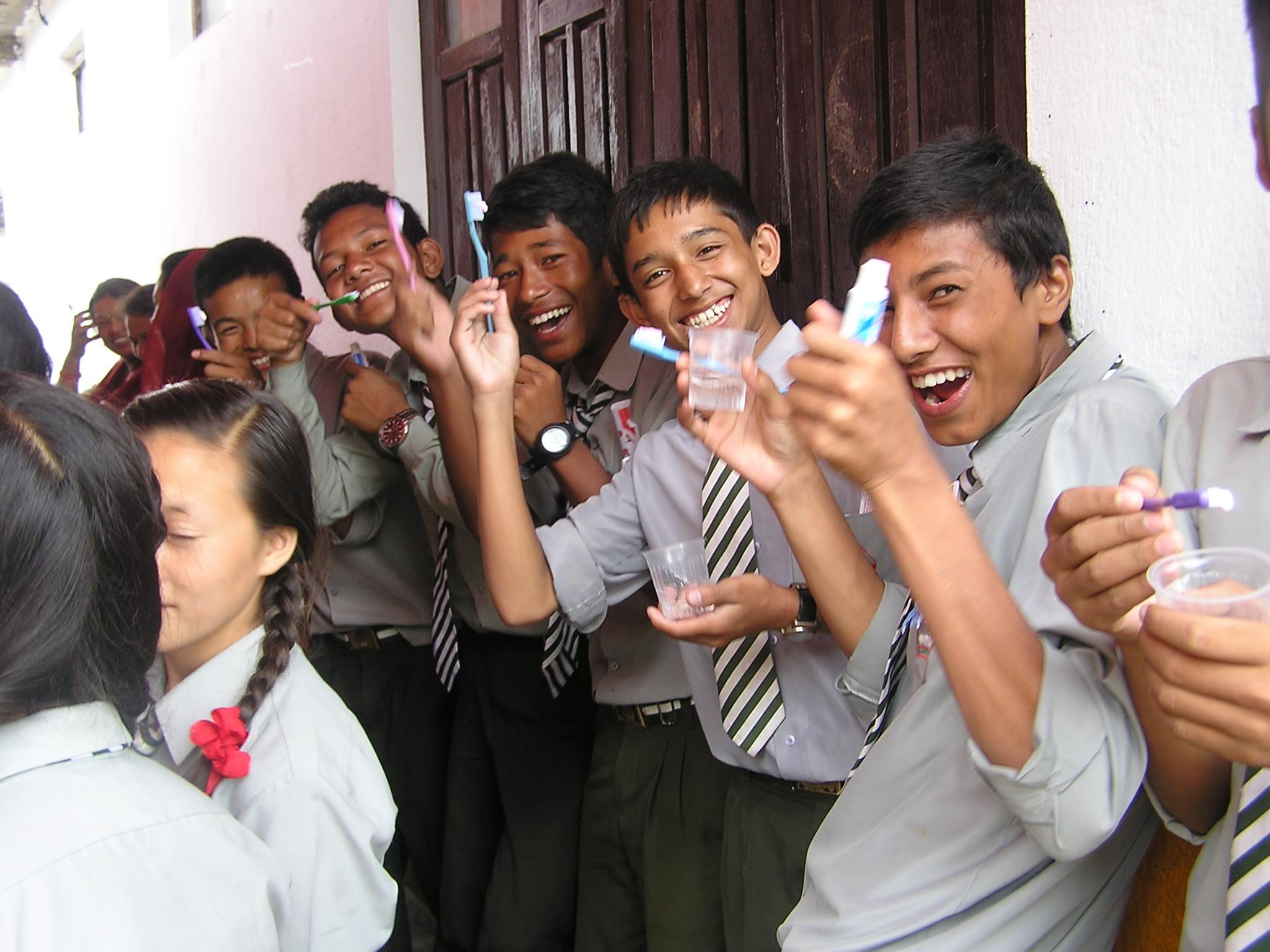 Group of children in a school with toothbrushes given to them during a dental awareness program run by Projects Abroad Dentistry interns in Nepal.